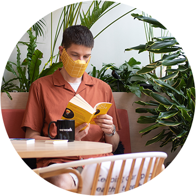 A man sitting at a table wearing a MOO Paper Face Mask while he reads a book